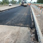 Roller compacts newly-laid material