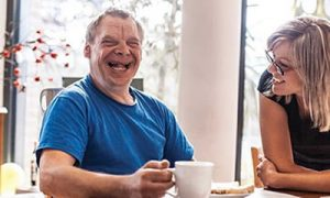 man smiling sitting at a table with a cup of tea