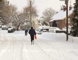 road covered in snow with person walking down the road, a person in the background is shoveling snow from their drive