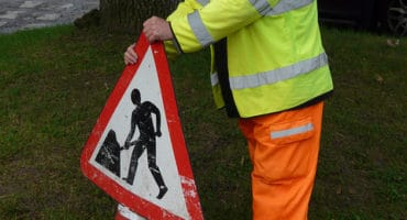 workman in hi vis putting up traffic cone with road works sign