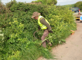 man cutting back weeds on devon country road