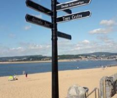 Black multi directional fingerpost sign on pavement next to the sandy beach at Exmouth