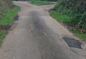 country road with pot holes rapired with tarmac