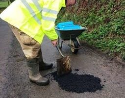 man in hi vis jacket with wheelbarrow and spade filling in pothole