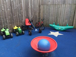 A photograph of some of the toys in the outdoor play area in the garden at Barnes: two little tractors, a bicycle, a go-cart, a large blue rubber ball and a see-saw.