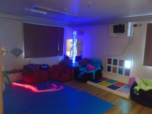 A photograph of the sensory room at Welland House: with fibreoptic lights, a bubble tube, beanbags to sit on, and a colour and light board on the wall.