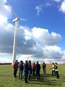 Wind turbine in field with group of people standing at base