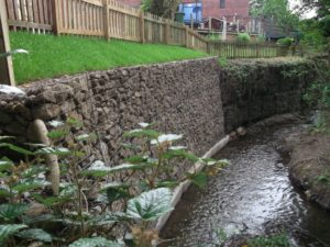 An example of a well installed gabion wall on a concrete base, alongside another gabion wall being undermined at the base and starting to fail