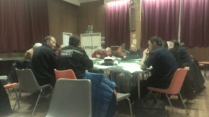 Photo of individuals around table discussing community emergency plan