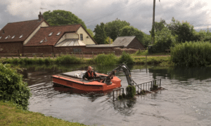 Ranger Craig Saunderson operating the Weedboat clearing weed from the canal