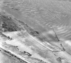 A black and white aerial photograph of the shoreline, with a fish trap visible as a low V-shaped structure .