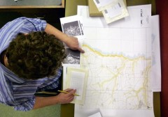 A colour photograph, taken from above, showing an aerial photograph interpreter seated at a desk, locating the position of 1940s black and white photographs on a modern map.