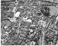Totnes from the air in 1990. The town's development can be seen in its layout. The circuit of the Saxon walls can be seen as well as the Norman castle that was built on top of earlier residential properties. The medieval church dominates much of the town centre and the market square is also prominent. Medieval tenement strips ('burgage' plots) can be seen on either side of the main street, inside and outside the walls. Early 20th century suburban terraces are set out in ranks on the slopes below the castle (Photo: Frances Griffith, Devon County Council).