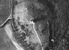 A black and white aerial photograph shows a tall, narrow building of triangular plan on a hilltop,