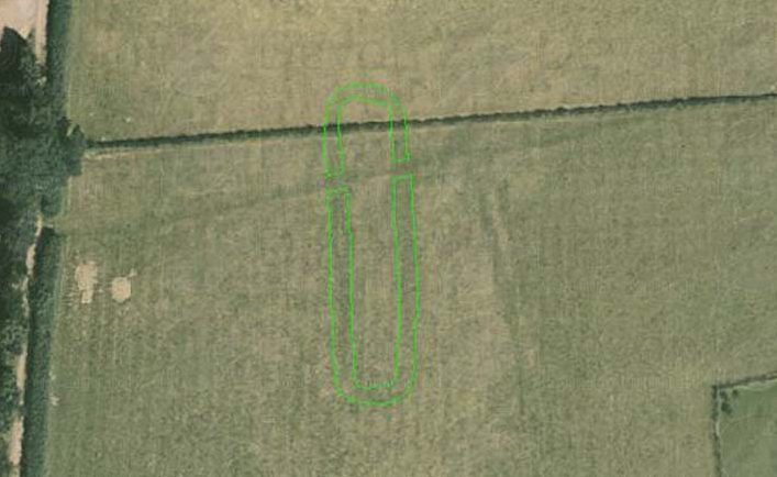 A colour aerial photograph shows a dark oblong cropmark, crossed by a straight field boundary.