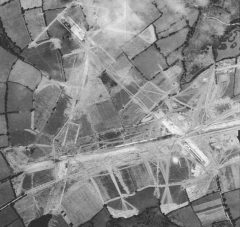 A black and white aerial photograph showing the three airfield runways in a trianguar formation crossing numerous fields. Hedgebanks within this area have been removed and their former position is visible as linear stretches of bare earth.