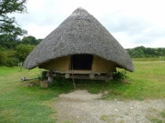 A ground photographs of a circular building with a thatched roof, raised above the ground surface by wooden posts.