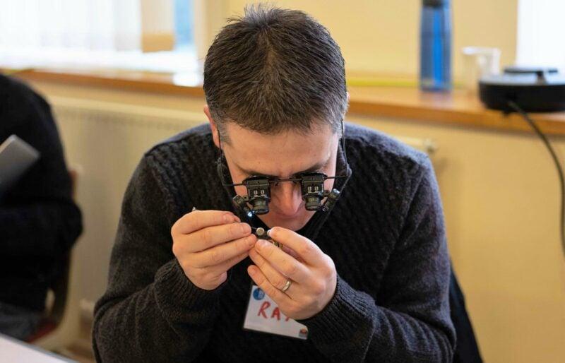 A volunteer fixer wearing watch-makers eye glasses