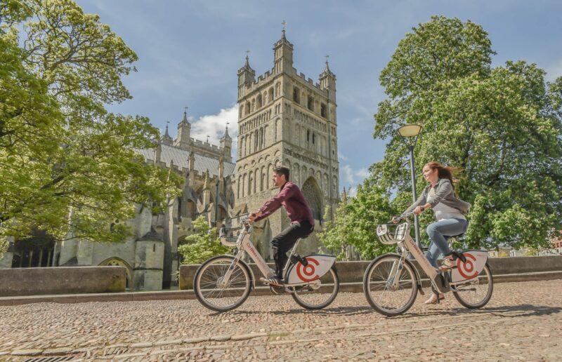Two cyclists cycling past Exeter Cathedral