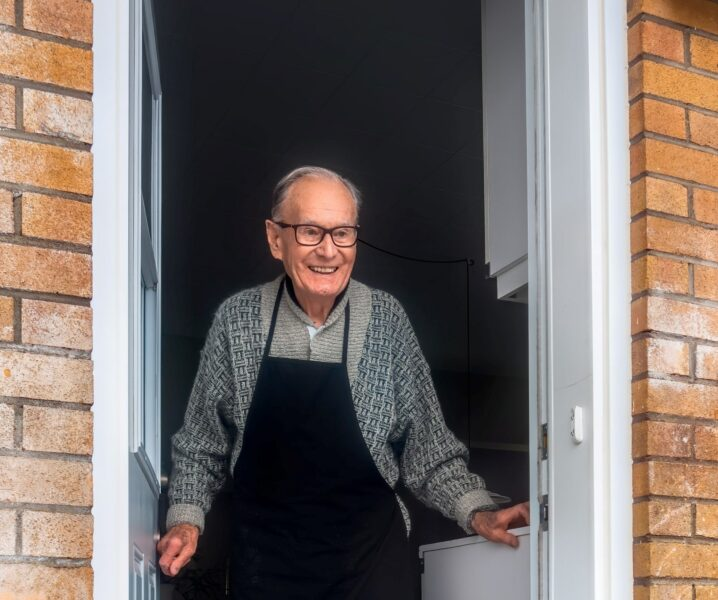 elderly man stood at a front door smiling