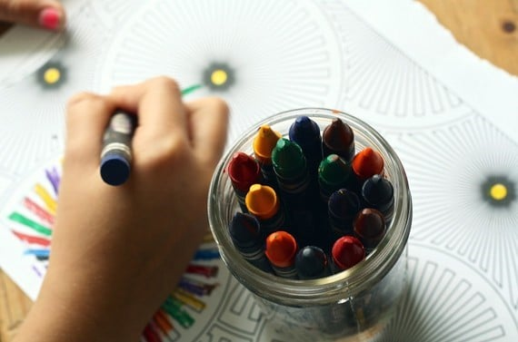 child's hands using crayons to draw