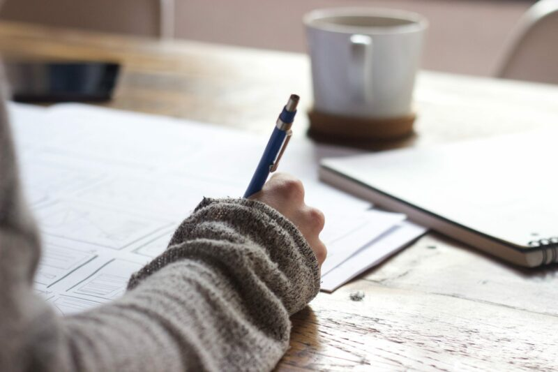 youn g person's arm and hand holding a pen, writing at a desk