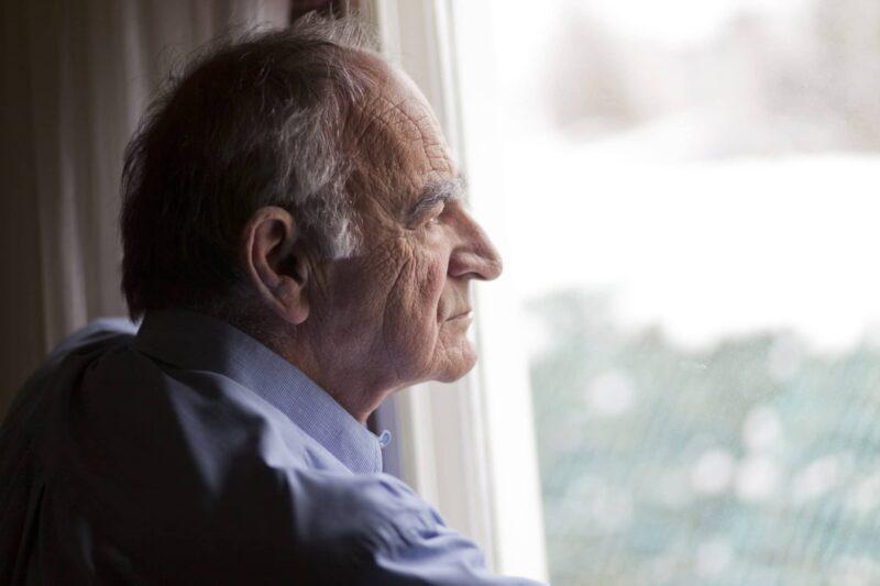 older gentleman looking out of a window