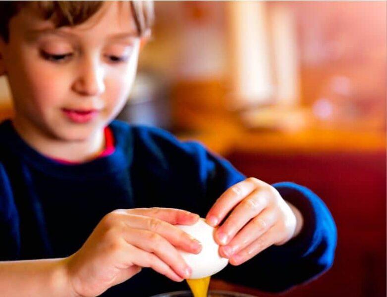 young boy cracking an egg