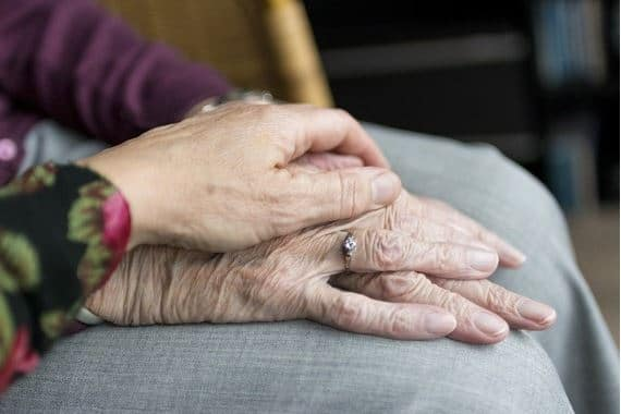 a caring hand resting over the hand of a vulnerable person