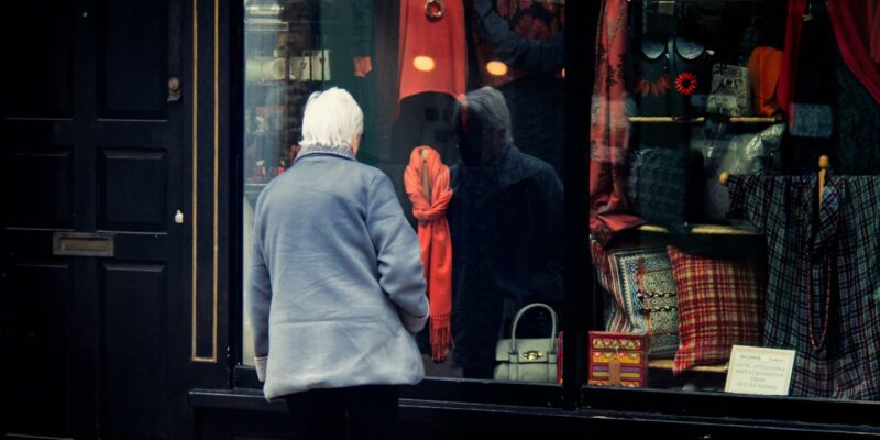 man stood looking into a shop window