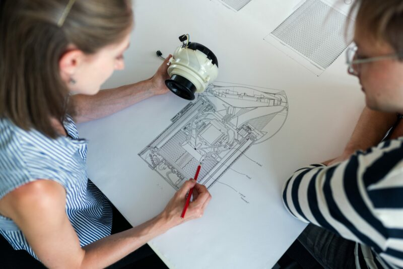 Two engineers looking closely at a line-drawing