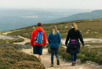 Three people walking along a path across moorland