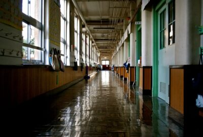 A long school corridor, with classrooms off to the right and windows on the left