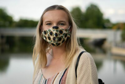 Young person wearing a face covering, stood in a park with a river in the background