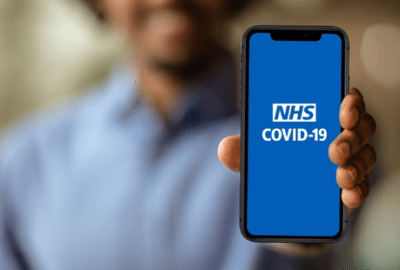 Person holding up their mobile phone to the camera, with the NHS Covid-19 app on the screen