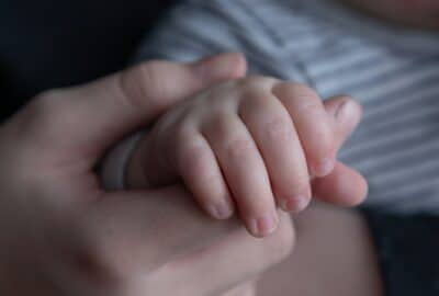 close up image of mother's hand holding baby's hand