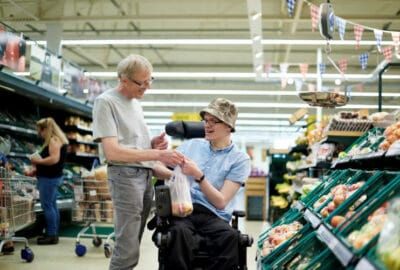 gentleman in a wheelchair being supported by his care worker while shopping in a supermarket