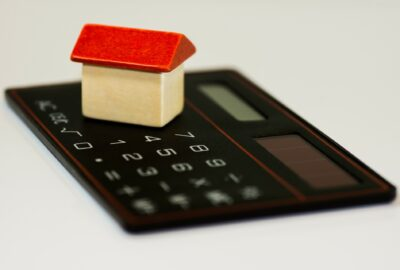 a calculator with a model house by it, indicating household bills