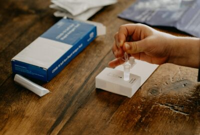 a person sat at a table taking a lateral flow test, squeezing a liquid into a small plastic tube