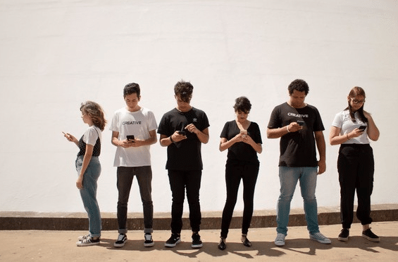 young people, stood in a line, on their mobile phones