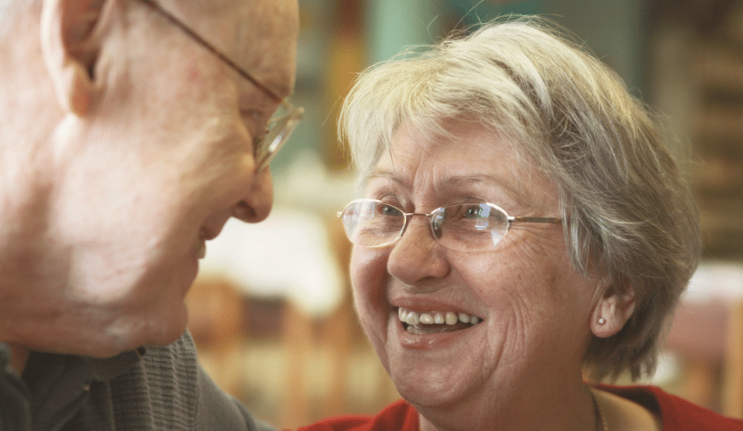 An older lady and man looking at each other and smiling