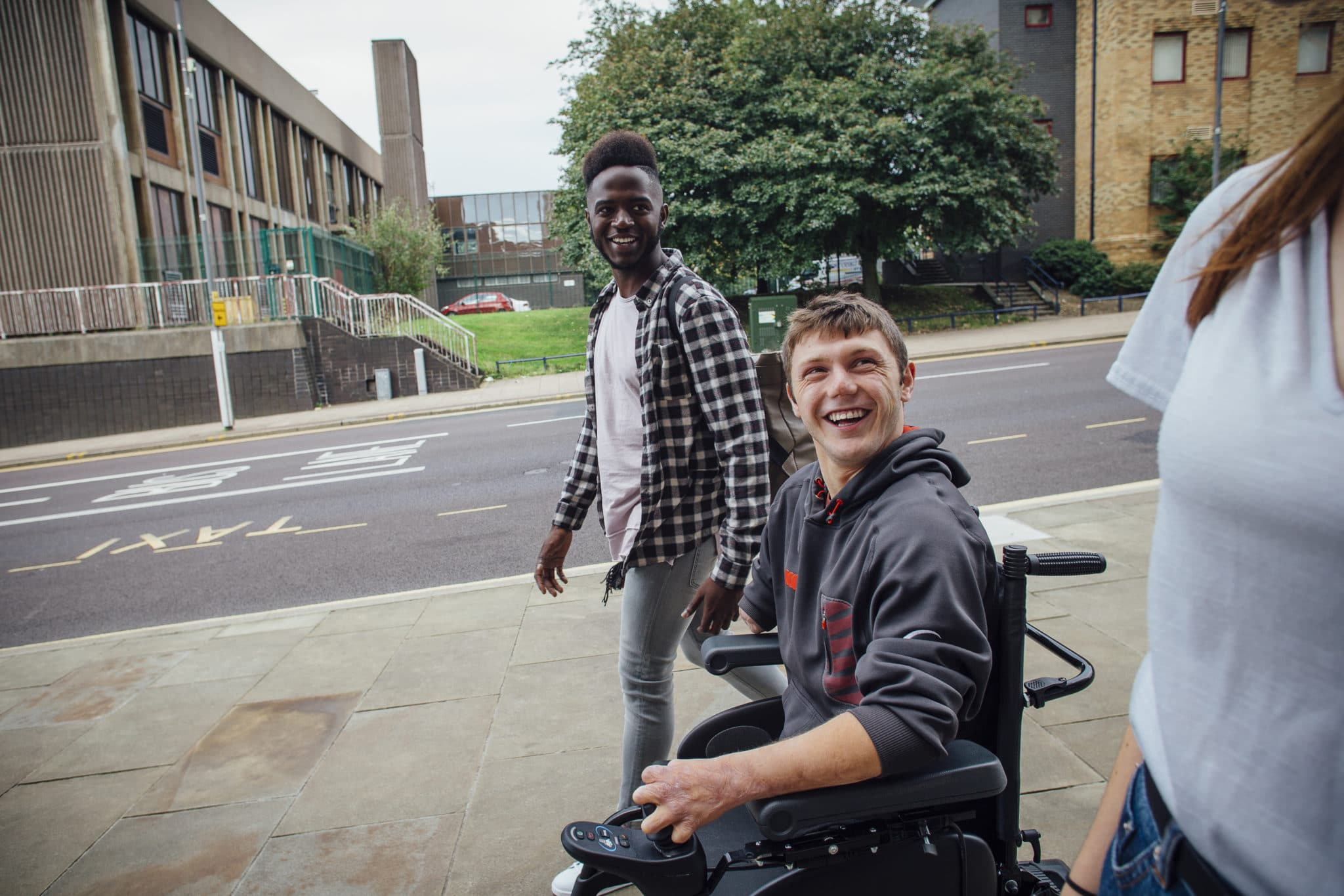 Three young adults on a pavement, one in a wheelchair, looking happy