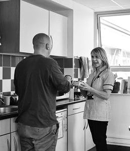 Two people having a conversation in a kitchen