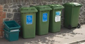 Some green recycling bins lined up in front of a wall
