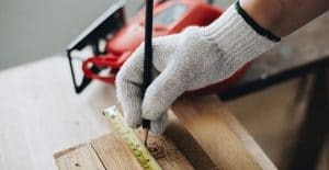 A close-up of a tradesman's hand measuring some wood with a measuring tape and a pencil
