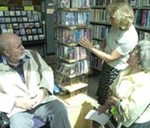 man in a wheelchair talking to a lady in library