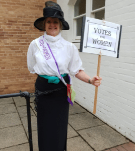 Picture of Suffragette Sue with 'votes for women' sign, chained to a railing at County Hall