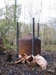 Charcoal kiln burning with logs and a bag of charcoal