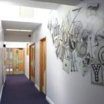 school corridor with art partly covering the walls