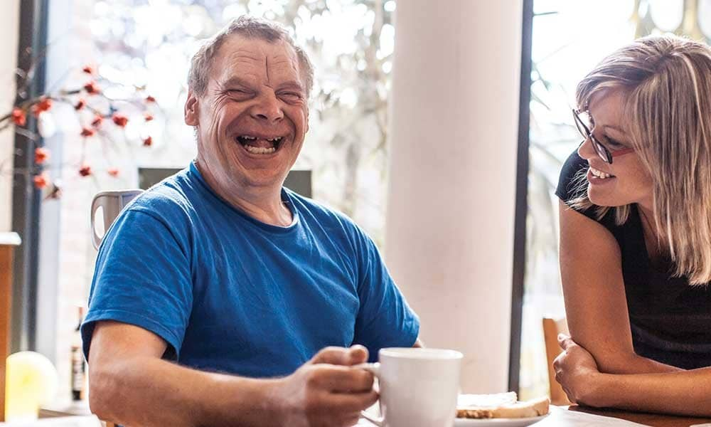 Man laughing whilst drinking a cup of tea